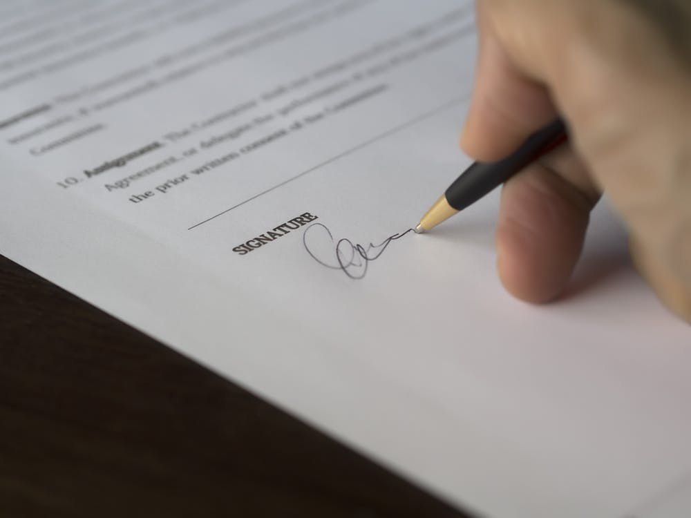 Person signing his signature on a document